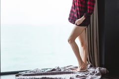 Beautiful slim legs of young woman in plaid shirt Royalty Free Stock Image