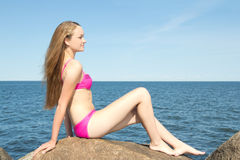 Beautiful slim model in pink bikini sitting on stone at rocky be Stock Photography