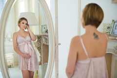 Beautiful slim pregnant girl with a tattoo on shoulder blade looking at herself in the mirror Royalty Free Stock Image