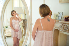 Beautiful slim pregnant girl with a tattoo on shoulder blade looking at herself in the mirror.  Royalty Free Stock Images