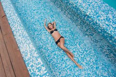 Beautiful slim sexy blonde girl in a black bathing suit lays in the pool Royalty Free Stock Photos