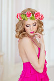 Beautiful slim sexy blonde in a red dress and a wreath of flower Stock Photo