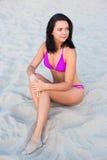 Beautiful slim sexy woman in bikini sitting on beach Royalty Free Stock Photography