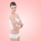 Beautiful slim sexy woman in cotton underwear posing over beige Royalty Free Stock Image