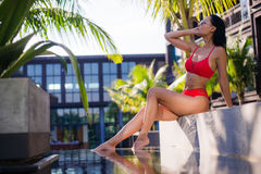 Beautiful slim sexy woman wearing red bikini relax near outdoor water pool on resort Royalty Free Stock Image
