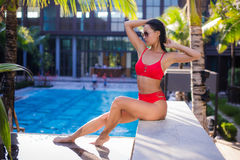 Beautiful slim sexy woman wearing red bikini relax near outdoor water pool on resort Stock Photos