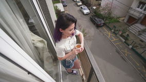 Beautiful slim sexy young woman drinking tea in balcony stock video