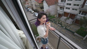Beautiful slim sexy young woman iwith a cup of tea n balcony stock video