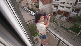 Beautiful slim sexy young woman with purplr hair in balcony stock footage