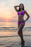 Beautiful slim sporty woman in bikini posing over sea background Royalty Free Stock Photography