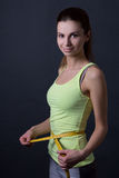 Beautiful slim sporty woman with measure tape over grey Stock Images