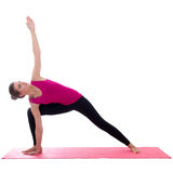 Beautiful slim sporty woman standing on pink mat in yoga pose is Stock Image
