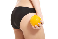 Beautiful slim and supple female buttocks with orange. Isolated on white Stock Photos