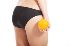 Beautiful slim and supple female buttocks with orange. Isolated on white Stock Photography