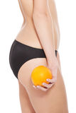 Beautiful slim and supple female buttocks with orange. Royalty Free Stock Photography