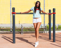 Beautiful slim tanned fitness girl `s back with hands on top. Posing outdoor in stylish white shorts and t-shirt. Sunny day Royalty Free Stock Photography