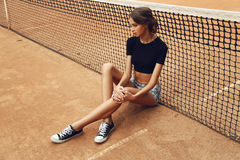 Beautiful slim tennis girl with dark hair wears sports clothes, posing on tennis court Stock Image
