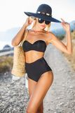 Beautiful slim woman in big hat on the beach royalty free stock photo
