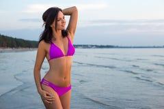 Beautiful slim woman in bikini posing over sea background Royalty Free Stock Image