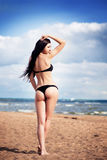 Beautiful slim woman in black bikini. Beach, sand blue sky Royalty Free Stock Photography