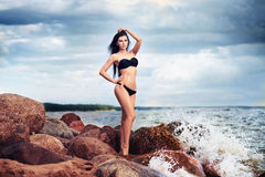 Beautiful slim woman in black bikini. Beach, sand and stones Royalty Free Stock Photos