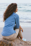 Beautiful slim woman with curly hair sitting on a rock. By the sea. She is dressed in beige trousers and a denim shirt. Back view royalty free stock photos