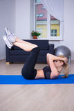 Beautiful slim woman doing exercises for abdominal muscles Royalty Free Stock Images