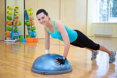 Beautiful slim woman doing push ups with bosu ball in gym Royalty Free Stock Photo