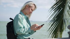 Beautiful slim woman with long blonde hair and green shirt standing near palm tree and using smartphone over background. Young beautiful slim woman with long stock footage