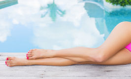 Beautiful slim woman's legs by the pool Stock Photos