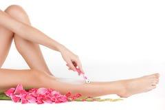 Beautiful slim woman shaving legs. Stock Image