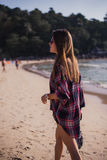 Beautiful slim woman in shirt, shorts and fashion sunglasses walk on beach. View from back. Beauty cute girl on a. Tropical beach sea ocean shore with luxury Stock Photos