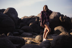 Beautiful slim woman in shirt, shorts and fashion sunglasses walk on big rocks. View from back. Beauty cute girl on a. Tropical beach sea ocean shore with large Royalty Free Stock Images