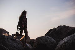 Beautiful slim woman in shirt, shorts and fashion sunglasses walk on big rocks. View from back. Beauty cute girl on a. Tropical beach sea ocean shore with large Royalty Free Stock Image