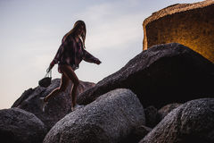 Beautiful slim woman in shirt, shorts and fashion sunglasses walk on big rocks. View from back. Beauty cute girl on a Royalty Free Stock Images