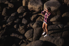 Beautiful slim woman in shirt, shorts and fashion sunglasses walk on big rocks. View from back. Beauty cute girl on a. Tropical beach sea ocean shore with large Royalty Free Stock Photography