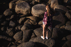 Beautiful slim woman in shirt, shorts and fashion sunglasses walk on big rocks. View from back. Beauty cute girl on a. Tropical beach sea ocean shore with large Royalty Free Stock Photo