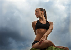 Beautiful slim woman sititng in twisted yoga pose Royalty Free Stock Photos