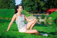 Beautiful slim woman in sportswear sitting in park Royalty Free Stock Photo