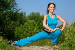Beautiful slim woman stretching outdoors Stock Photo