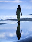 Beautiful, slim woman take a walk next to the sea. Beautiful woman walks next to the sea in long dress Royalty Free Stock Images