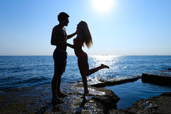 Beautiful slim young lovers standing on rock in sea, looking int Stock Photos