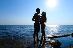 Beautiful slim young lovers standing on rock in sea, looking int Stock Photo