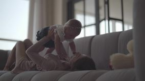 Beautiful slim young woman lying on the sofa raising her baby girl up. The mother playing with her child at home stock footage