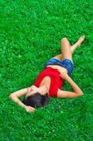 Beautiful woman is relaxing on the lawn. Beautiful slim young woman is relaxing on the lawn Royalty Free Stock Images