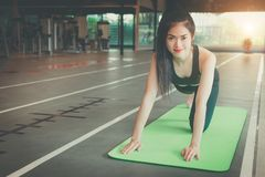 Beautiful slim young woman resting at gym. Muscular girl wearing sportswear, sitting on exercise mat. royalty free stock photography