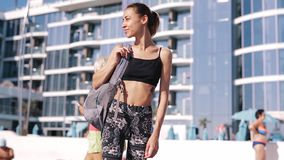 Beautiful slim young woman in sportswear on the coast against spa hotel. Happy female with sexy tanned body, perfect. Beautiful slim young woman in sportswear stock video
