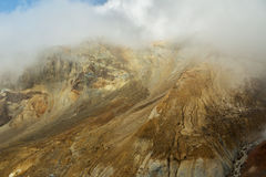Beautiful slopes Mutnovsky volcano shrouded in clouds. Royalty Free Stock Photography