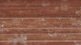 Beautiful slow motion b-roll footage of heay rain falling on a backyard deck. stock video footage