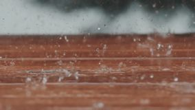 Beautiful slow motion b-roll footage of heay rain falling on a backyard deck. Shot in RAW on a cinema camera stock footage